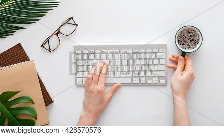 Woman Typing On Computer Keyboard And Drinking Coffee At Workplace. Flat Lay Office Desktop Workspac