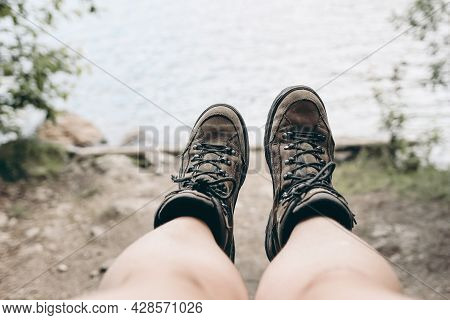 Closeup Of A Womans Legs And Old Leather Trekking Boots. Blurred Lake, River And Shrubs Background.
