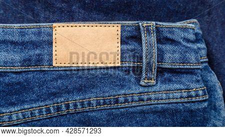 Brown Blank Leather Label Tag On Denim Pants Background. Blank Mockup Beige Leather Label. Blue Deni