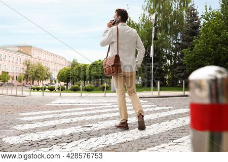 Young Man Talking On Phone While Crossing Street, Back View. Traffic Rules And Regulations