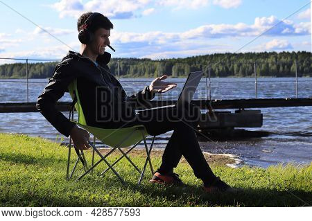 The Young Man Works Remotely . A Man Is Sitting On The Shore By The Water With Headphones And A Lapt