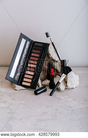 Decorative Cosmetics For Makeup On Stone Pedestal. Red Scarlet Lipstick Eyeshadow Makeup Brushes On