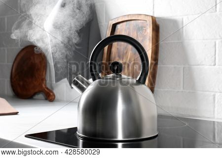 Steaming Kettle On Electric Stove In Kitchen
