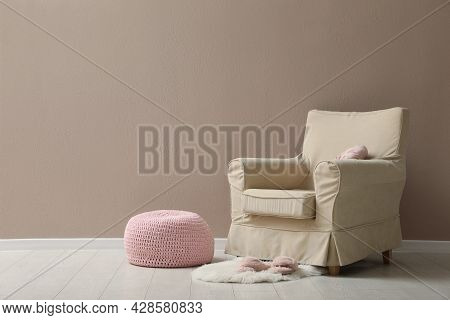 Knitted Pouf, Fuzzy Rug With Slippers And Armchair Near Beige Wall Indoors. Space For Text