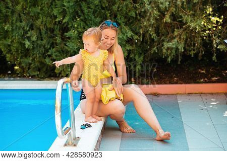 Summer Vacation. Happy Mother Sits With Little Daughter Near A Pool. Baby Girl In Swimsuit Point Wit