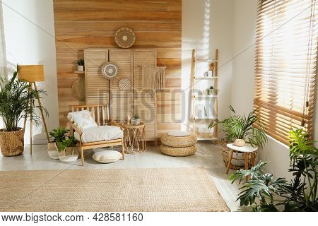Stylish Living Room Interior With Comfortable Wooden Armchair And Beautiful Houseplants