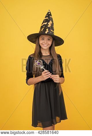 Happy Child Wear Witch Hat Holding Magic Wand To Create Enchantment On Halloween, Happy Halloween