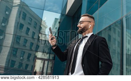 Mature Entrepreneur Man Listening To Music In Wireless Earphones And Surfing Internet On Smartphone