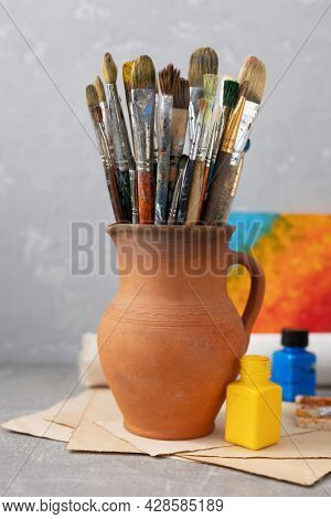 Paint brush in clay jug and art painter tool on table background texture. Paintbrush for painting as artistic paint still life. Abstract art concept