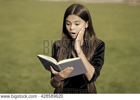 Learn To Discover. Surprised Child Read Book Outdoors. Retro School Supplies. Old-fashioned Educatio