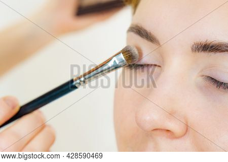 Face Painting. Makeup Artist Applying Shadows To Model Eye. Cosmetic Beauty Procedures, Make Up Stag