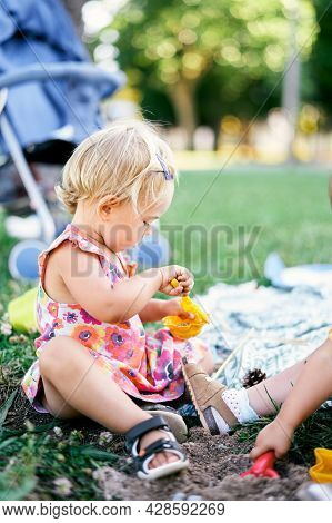 Little Girl Sits On The Lawn And Sculpts Sand Cakes