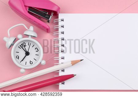 Spring-loaded Notepad,white Pencil, Pink Pen, Pink Stapler, Alarm Clock On A Pink Background.things