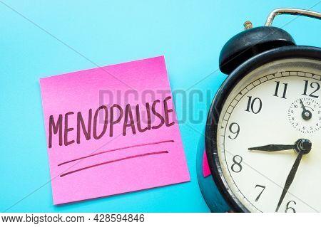 Menopause Word Handwritten On The Sticker And Alarm Clock.