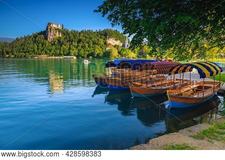 Traditional Touristic Wooden Pletna Boat Moored On The Waterfront. Pletna Rowing Boats On The Alpine