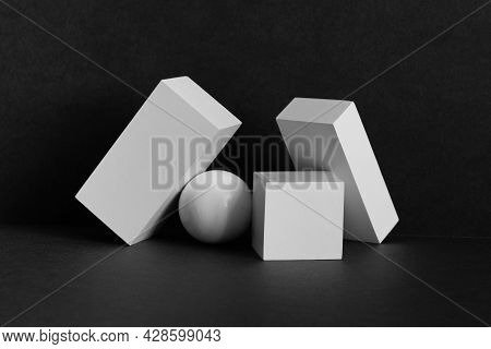 White Geometric Shapes On A Black Background. Platonic Figures Cube Rectangle And Sphere Arranged In