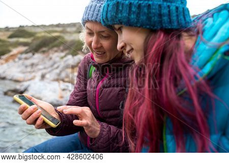 Two Tourists Are Looking At A Map On A Smartphone, Two Women Are Traveling Together, A Girl Is Looki