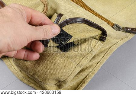 Close-up Of A Man's Hand Opening The Pocket Of A Shoulder Bag. Hook-and-loop Fastener. Canvas Casual