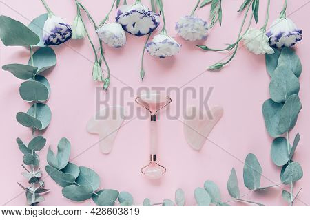 Facial Massage Kit Made From Rose Quartz. Face Roller And Gua Sha Massagers On Pink Pastel Backgroun