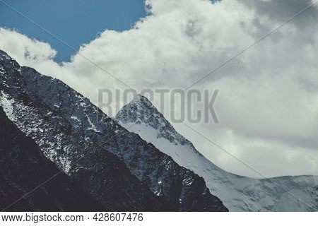 Atmospheric Mountain Landscape With High Snowy Peaked Top Under Cloudy Sky In Faded Tones. Gloomy Mo