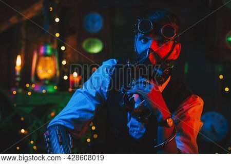 Cyberpunk Post-apocalypse Cosplay. A Man With Glasses And A Gas Mask In A Workshop With A Neon Light