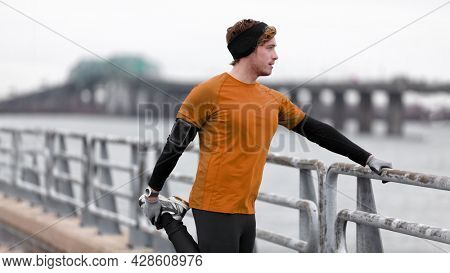 Runner man stretching legs on cold winter run listening to podcast or music with wireless earbuds earphones and mobile phone armband outdoor workout training.