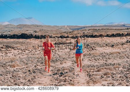 Sport athletes runners trail running training endurance in desert summer landscape. Man runner wearing compression sportswear. Fitness exercise workout fit Asian woman training for triathlon.