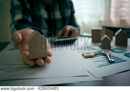 Real Estate Agents Showing Miniature House Models To The Customers And Calculate Price Of House On T