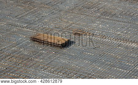 The Floor Of A Construction Site Prepared For Cement Flooring With A Framework Of Iron Rebar