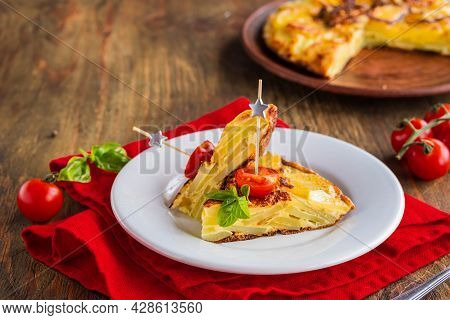 Sliced Spanish Tortilla, A Traditional Dish With Eggs And Fried Potatoes On A Clay Plate On A Wooden