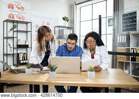 Team Of Three Multiracial Medical Practitioners, Working Together With Laptop, While Sitting At The