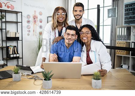 Group Of Four International Doctors In Lab Coat And Scrubs Sitting Together At Table And Using Lapto