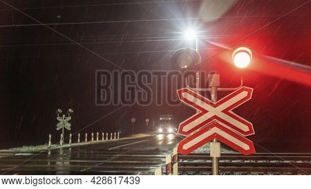 Train Crossing Gates Closed At Night. Train Grade Crossing With Blinking Or Flashing Lights While Tr