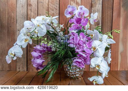 Beautiful Bouquet Of Arranged Orchid Flowers In A Silver Vase Given As An Emotional Sentiment.