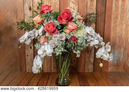Beautiful Bouquet Of Arranged Roses, Orchids, And Filler Leavesto Create An Expressive Sentiment Of