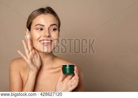 Young Woman Applies Moisturizer To Her Face And Smiles. Skin Care Concept