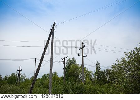 Poles With Electric Wires Among Green Trees Against A Blue Sky