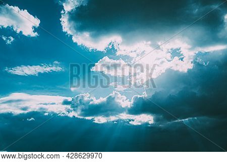 Sunrays Sunray Shine Through Dark Clouds In Cloudy Blue Sky. Natural Background. Natural Sky Backdro