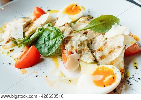 Classical Caesar Salad With Roasted Chiken, Eggs, Lettuce Leaves, Parmesan And Cherry Tomatoes On Th