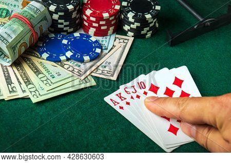 The Player Points With His Finger At A Winning Royal Flush Combination In A Poker Game On A Table Wi