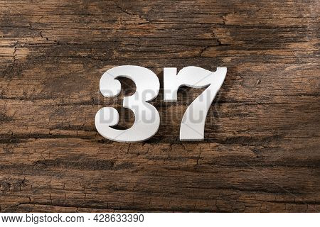 Thirty Seven 37 - White Wooden Number On Rustic Background