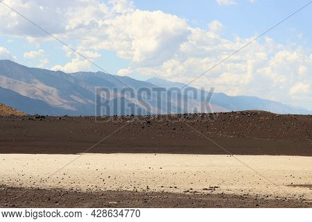 Sand Dunes Besides A Lava Field At Fossil Falls Crater On Arid Badlands With The Sierra Nevada Mount