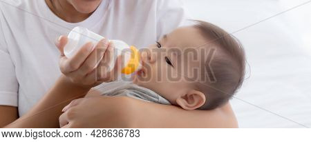 Young Asian Mother Embracing And Feeding Little Baby Girl With Bottle Of Milk At Home, Newborn Innoc