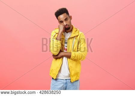 Studio Shot Of Bored Indifferent Good-looking Young Dark Skinned Guy With Beard And Afro Hairstyle L