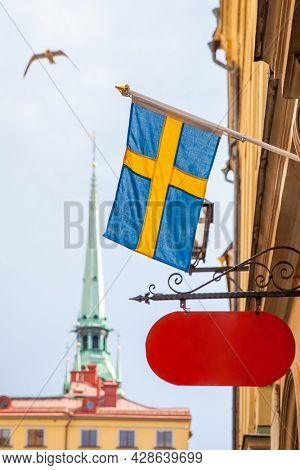 Old street in Stockholm with swedish flag and blank shop sign, Sweden. Shallow DOF, focus on the flag