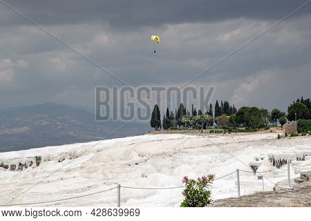Pamukkale, Turkey - 1 June, 2021: A Paraglider Hovers Over The Limestone Tuff Slopes On A Cloudy Sum
