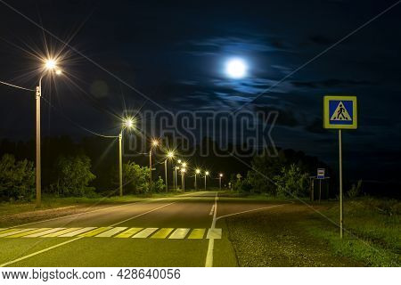 A Mysterious, Gloomy View Of An Asphalt Road With A Pedestrian Crossing, Road Signs, Bright Street L