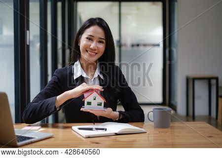 A Real Estate Agent Demonstrates The House Model To Clients Interested In Purchasing House Insurance