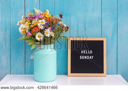 Happy Sunday Words On Black Letter Board And Bouquet Of Bright Wildflowers In Tin Can Vase On Table