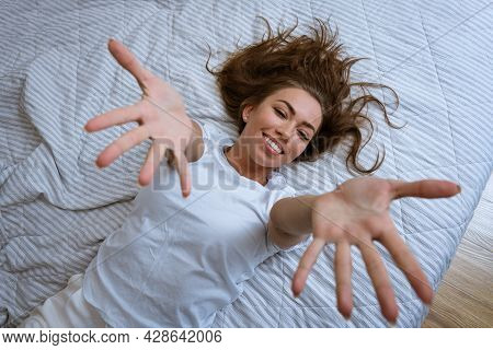 Lazy Morning Concept. Beautiful Happy Woman Wakes Up Lying In Bed And Stretches Her Arms Up. Attract